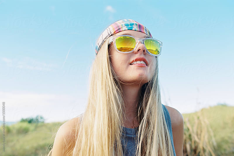 blonde girl with mirrored clear sunglasses and rainbow headband by wendy laurel for Stocksy United