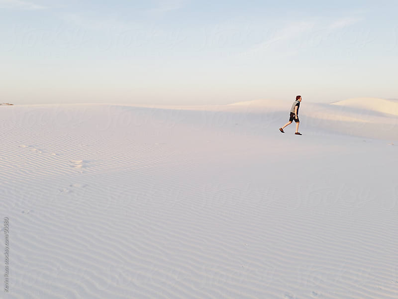 Lone White Sand Dune Walking Man by Kevin Russ for Stocksy United