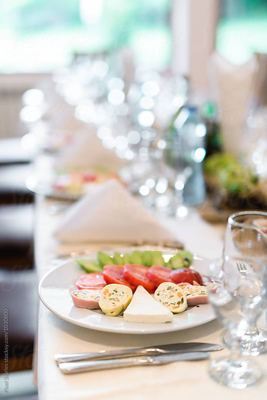 Long table with served salad for wedding reception by Pixel Stories for Stocksy United
