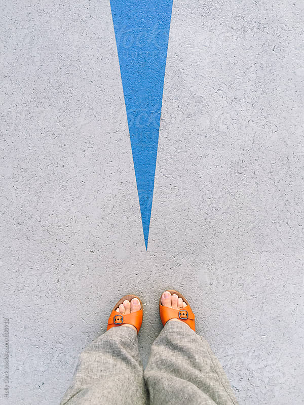 Looking down in a woman's feet wearing orange sandals by Holly Clark for Stocksy United