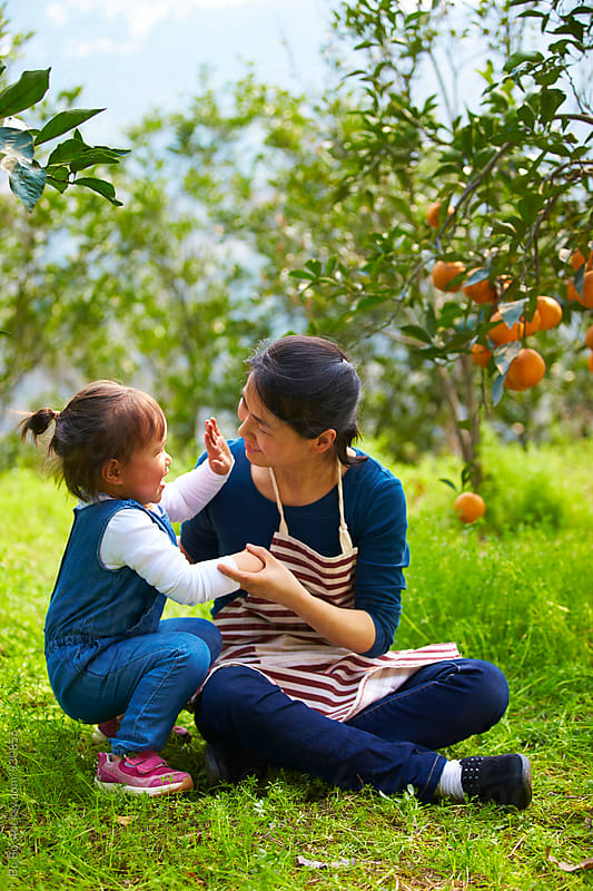 happy asian mother with her daughter in the orange farm by Bo Bo for Stocksy United