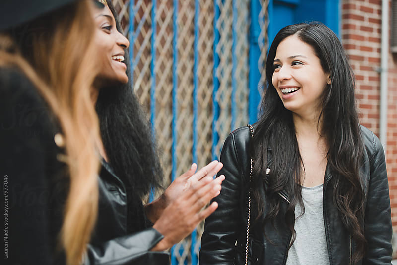 Young women talking and laughing outside by Lauren Naefe for Stocksy United