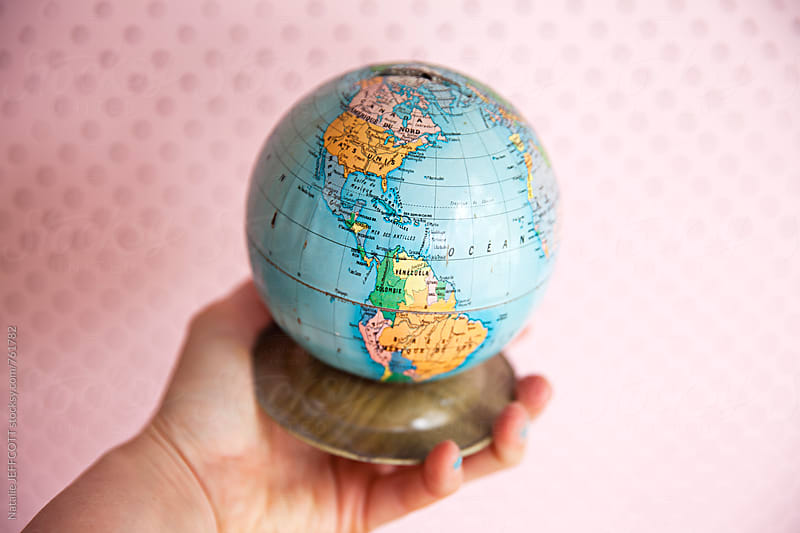 Holding a vintage French world globe money tin in hand by Natalie JEFFCOTT for Stocksy United