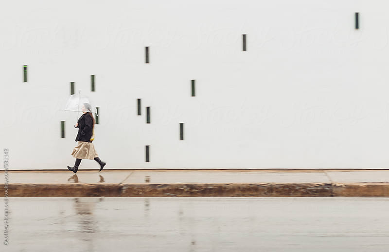 Woman Running in the Rain in the City by Geoffrey Hammond for Stocksy United