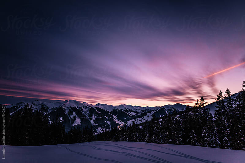 snowcovered austrian mountain landscape at sunset by Leander Nardin for Stocksy United