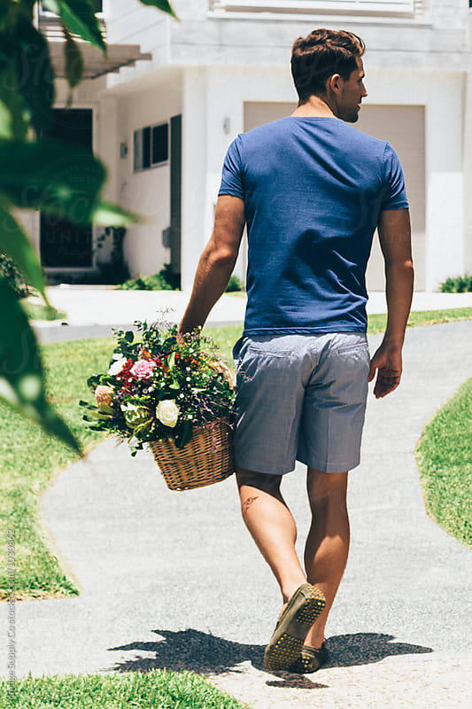 Young man walking carrying basket with breads and flowers by Image Supply Co for Stocksy United