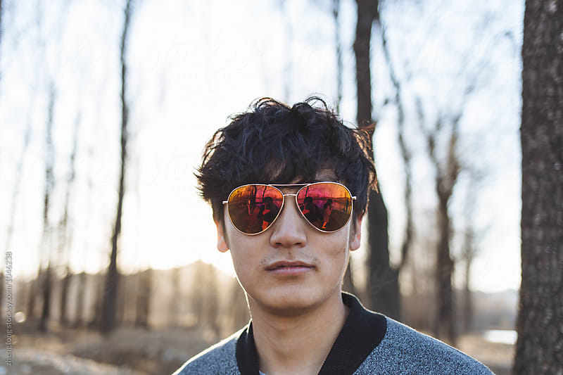 young man in the woods by zheng long for Stocksy United