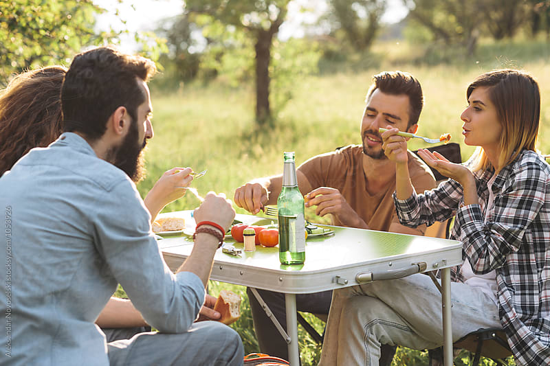 Group of friends eating and chatting outdoors by Aleksandar Novoselski for Stocksy United