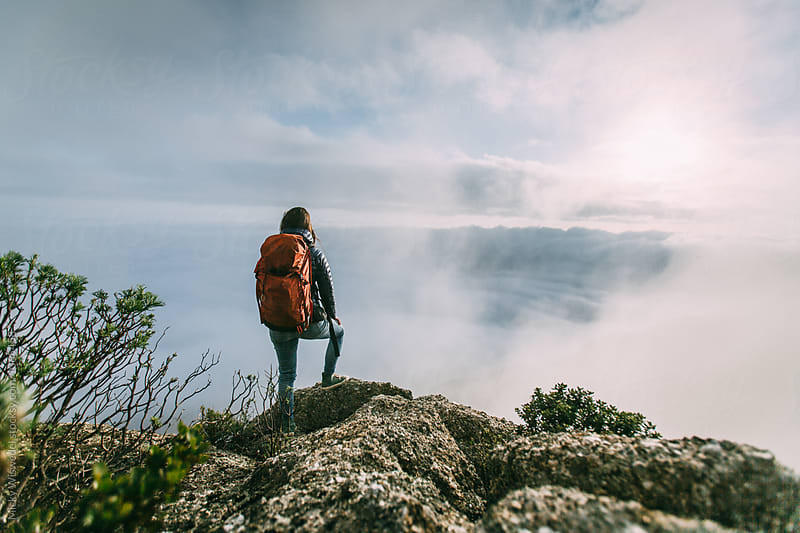 Hiker on a mountain summit overlooking scenic clouds at sunset by Micky Wiswedel for Stocksy United