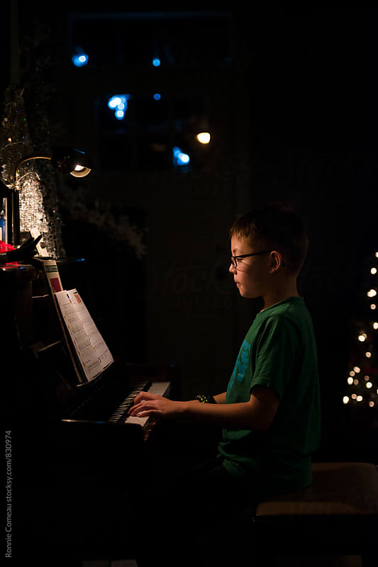 Boy Playing Piano by Ronnie Comeau for Stocksy United