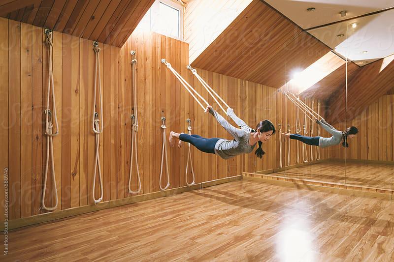 Young woman practicing acro yoga in studio by MaaHoo Studio for Stocksy United