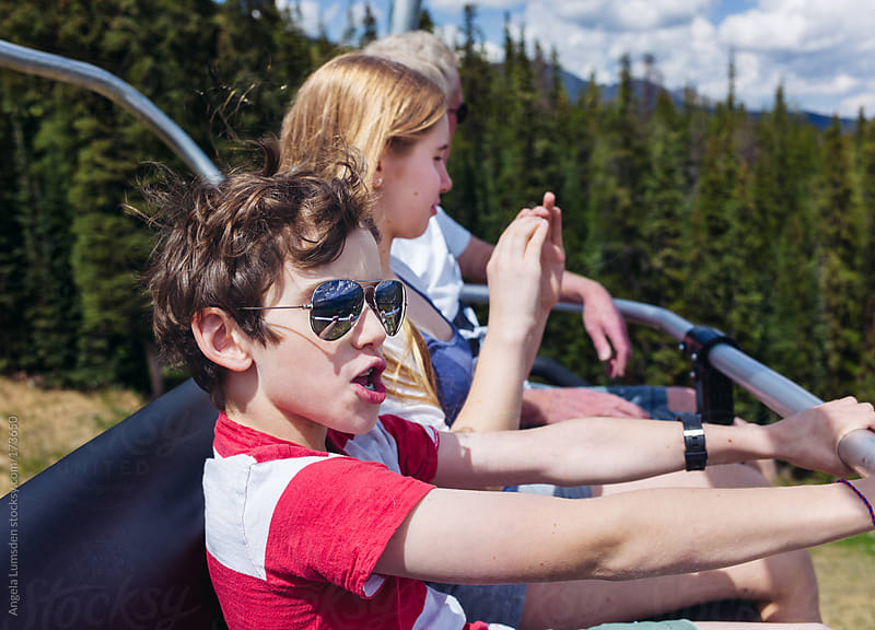 Boy having fun riding a chairlift in summer by Angela Lumsden for Stocksy United