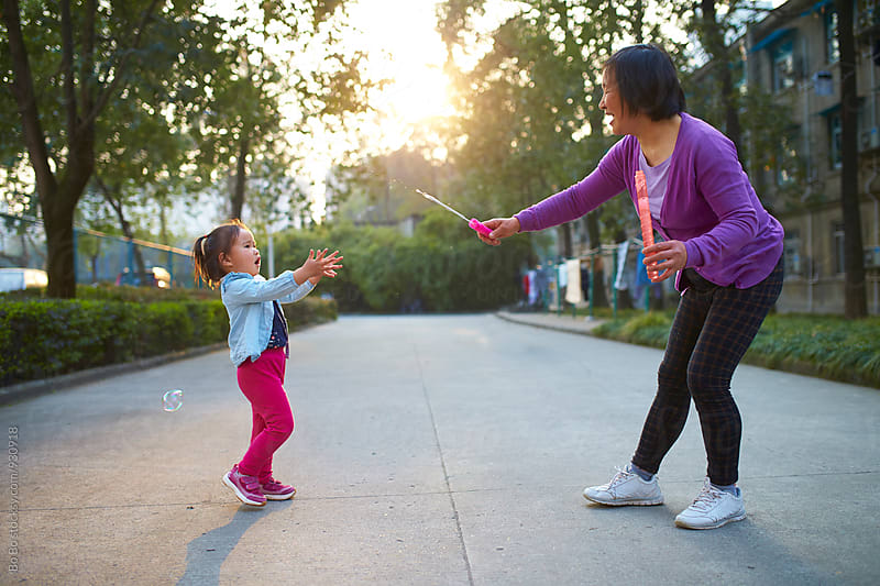 little asian girl playing with her grandmother outdoor by cuiyan Liu for Stocksy United