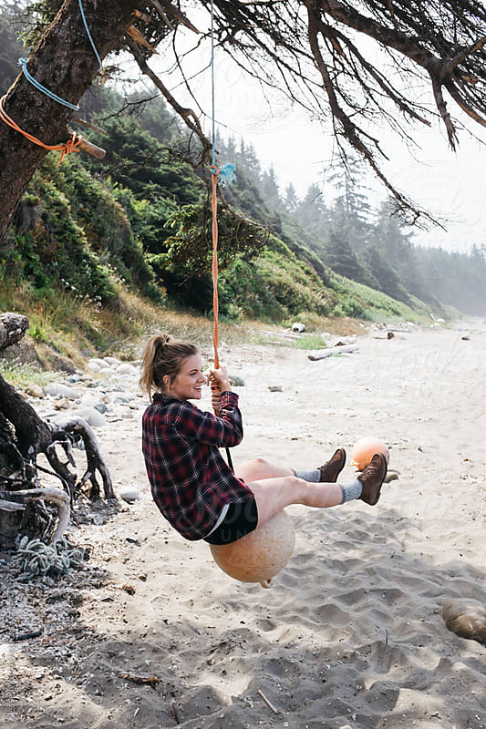 girl swings from recycled buoy on beach by Jesse Morrow for Stocksy United