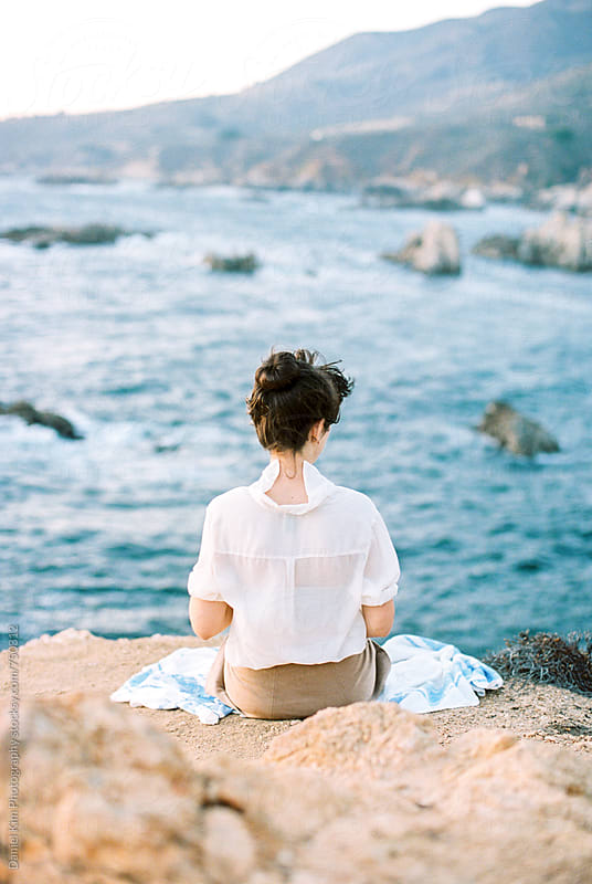 Woman sitting on seaside cliff by Daniel Kim Photography for Stocksy United