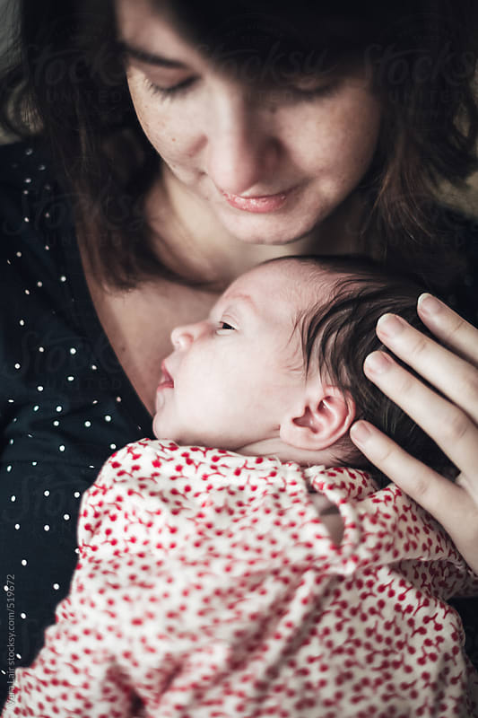 Mother Holding Sleeping Newborn girl by Vera Lair for Stocksy United