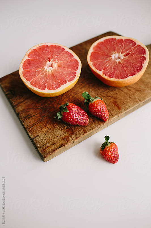 Grapefruit and strawberries on a wooden cutting board by KATIE + JOE for Stocksy United