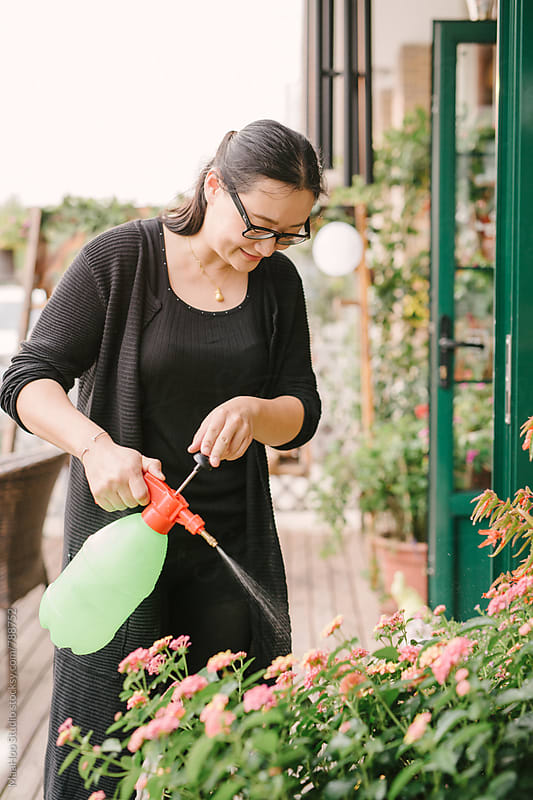 Female store owner watering the plants outside her shop by MaaHoo Studio for Stocksy United