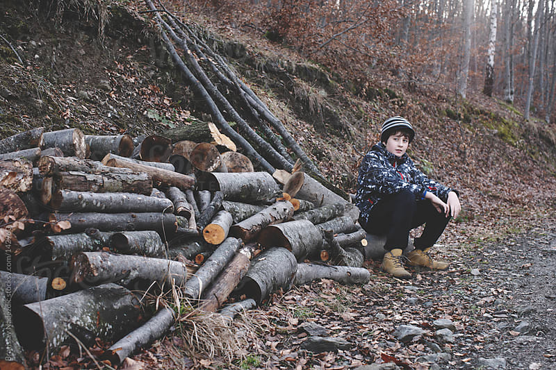 Young boy sitting on trunk in the wood by Bratislav Nadezdic for Stocksy United