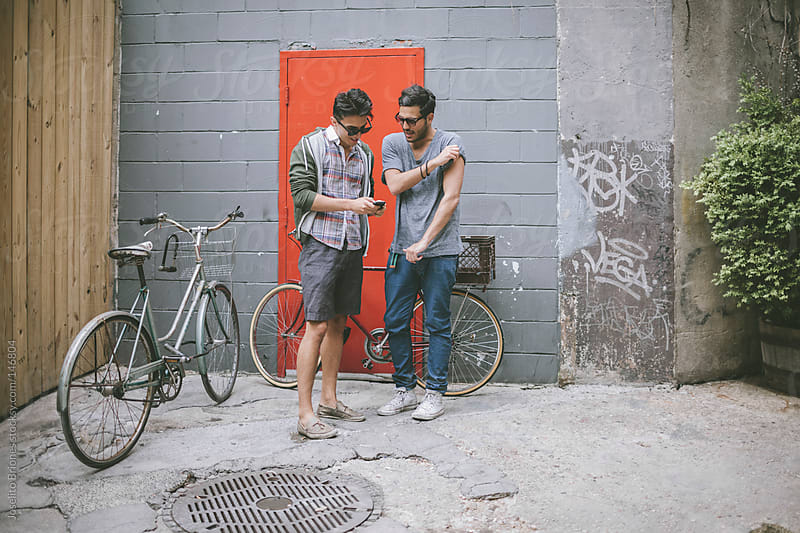 Casual Friends Talking about Smartphone in a City Courtyard by Joselito Briones for Stocksy United