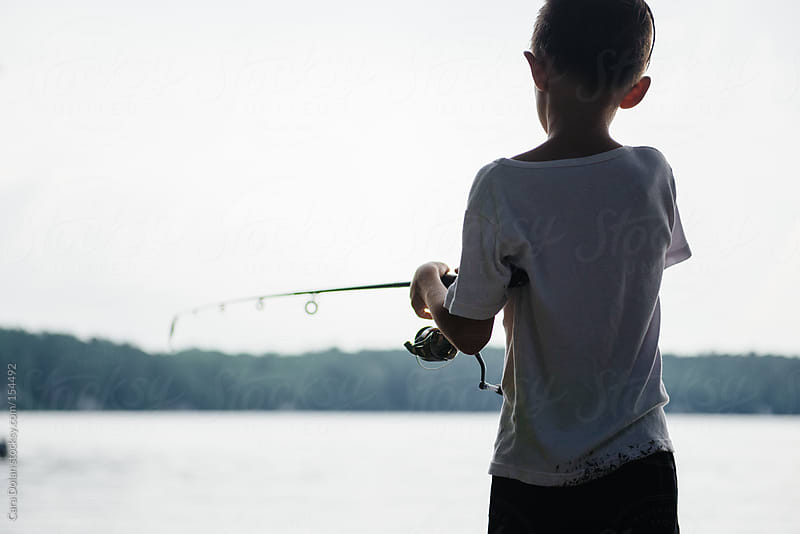 Boy fishes on a lake at sunset by Cara Dolan for Stocksy United