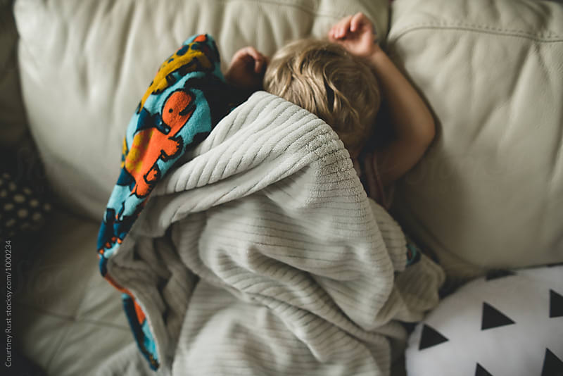 Boy hiding on couch under blanket by Courtney Rust for Stocksy United