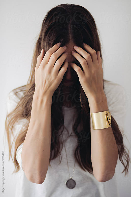 Young beautiful woman with long brown hair covering her face with hands by Maja Topcagic for Stocksy United
