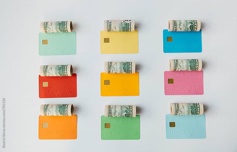 Colored credit cards with money rolls over them by Beatrix Boros for Stocksy United