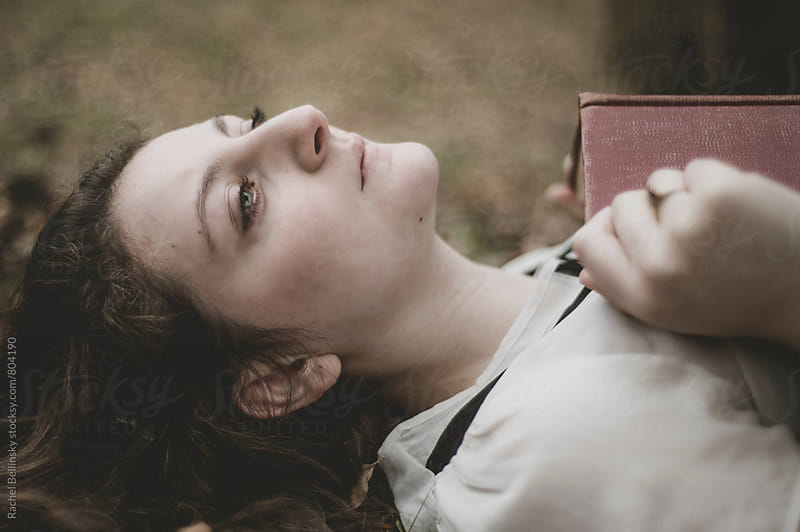 A young woman daydreams with a book on her chest in the woods by Rachel Bellinsky for Stocksy United