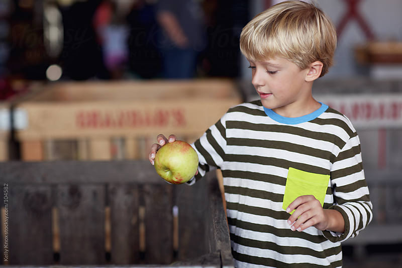 boy chooses an apple from a crate by Kelly Knox for Stocksy United