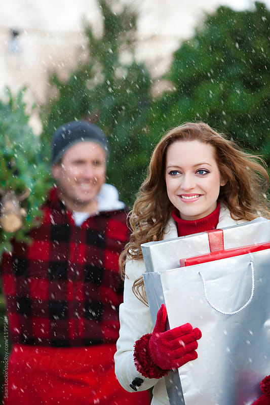 Tree Lot: Man Helps Woman with Christmas Tree by Sean Locke for Stocksy United