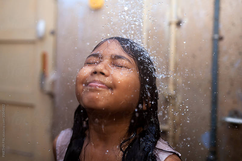 A girl enjoy shower bath in summertime,India by PARTHA PAL for Stocksy United