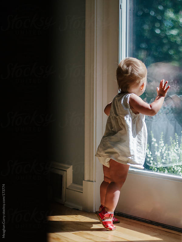 toddler looking through a glass door out to a garden by Meaghan Curry for Stocksy United
