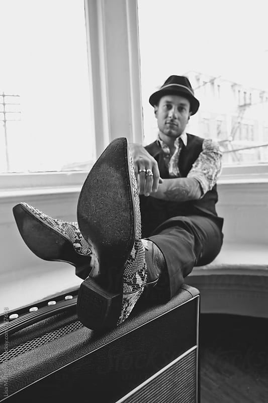 man sitting with alligator boots resting on top of  amplifier by Lisa MacIntosh for Stocksy United