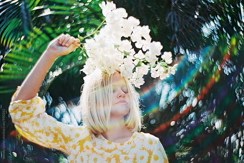 portrait of girl in yellow dress with white florals and rainbow flare by wendy laurel for Stocksy United