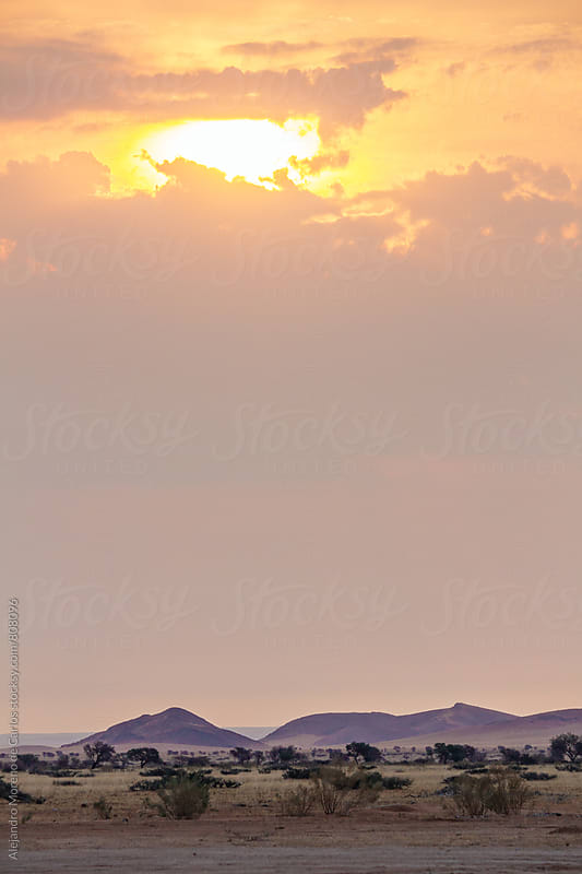 Beautiful sunset between the clouds over the desert with some hilly mountains in the background by Alejandro Moreno de Carlos for Stocksy United