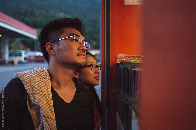young couple in the expressway service area by zheng long for Stocksy United
