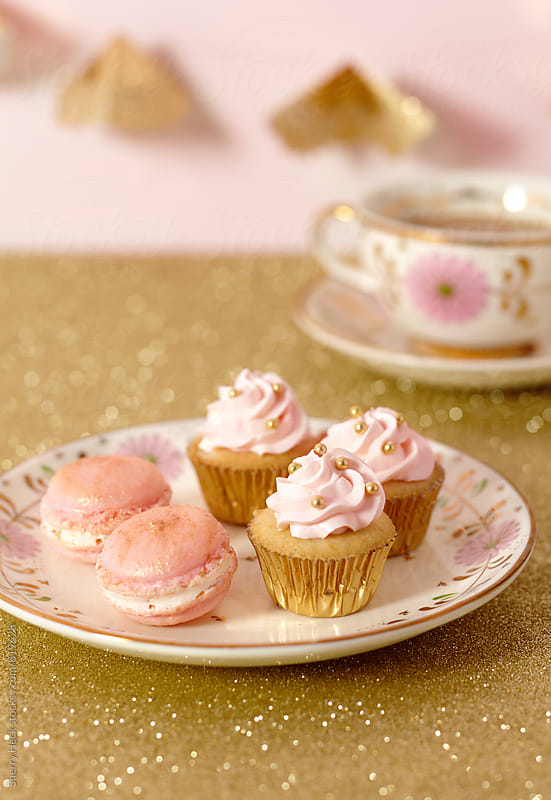 Pink Macaroons, mini cupcakes and tea on gold glitter background by Sherry Heck for Stocksy United