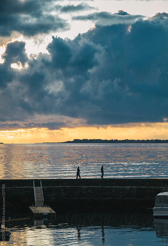 Two people walking through a dock at Sunset by VICTOR TORRES for Stocksy United