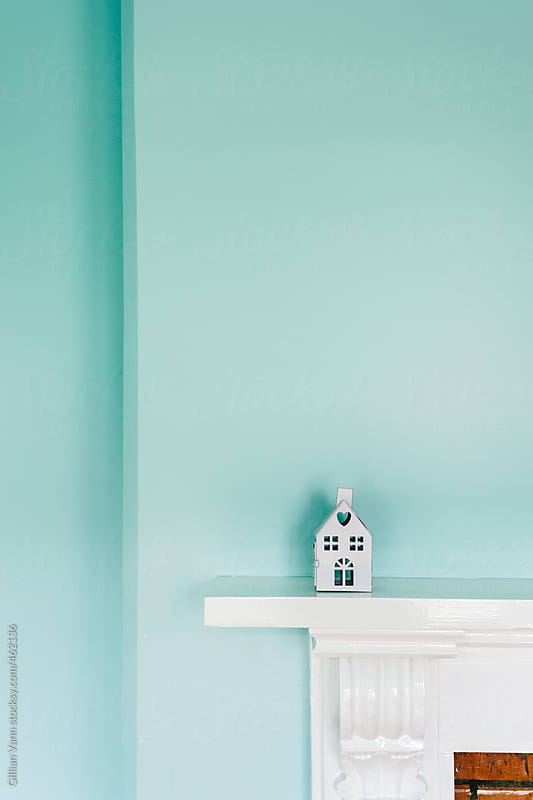 mini house on mantlepiece against a blue painted wall by Gillian Vann for Stocksy United