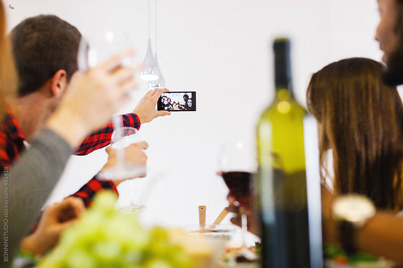 A selfie of group of friends making a toast with their wine glasses. by BONNINSTUDIO for Stocksy United