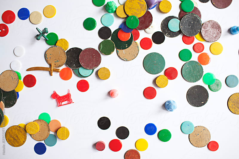 a collection of colourful vintage game pieces scattered on a white background by Natalie JEFFCOTT for Stocksy United