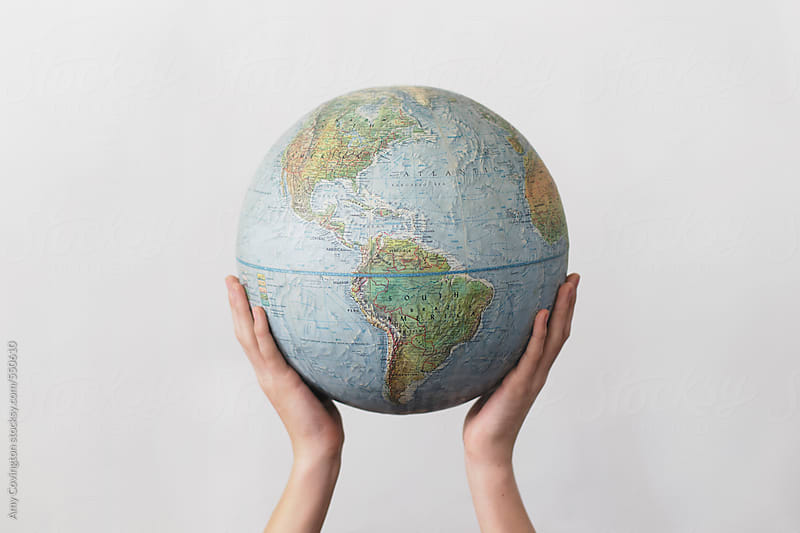 World globe held by two hands by Amy Covington for Stocksy United