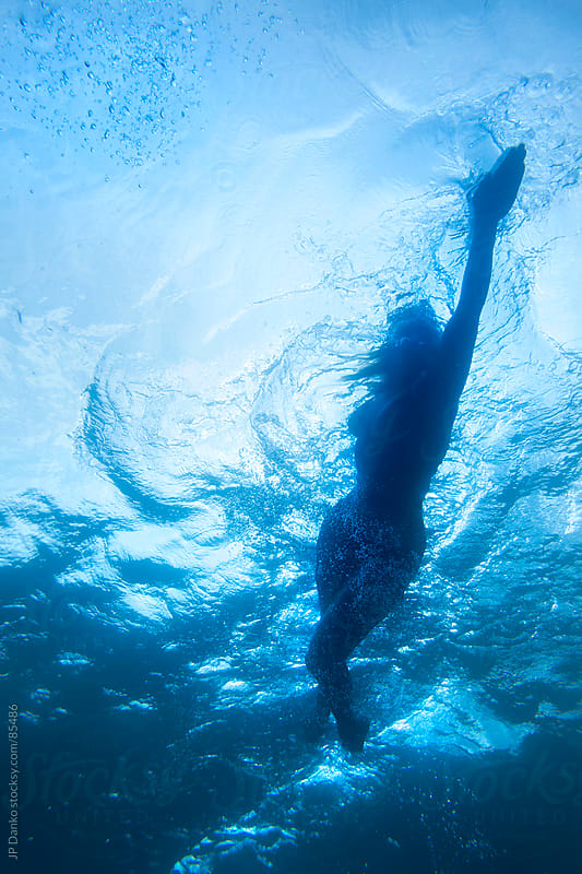 Female Athlete Swimming Underwater by JP Danko for Stocksy United
