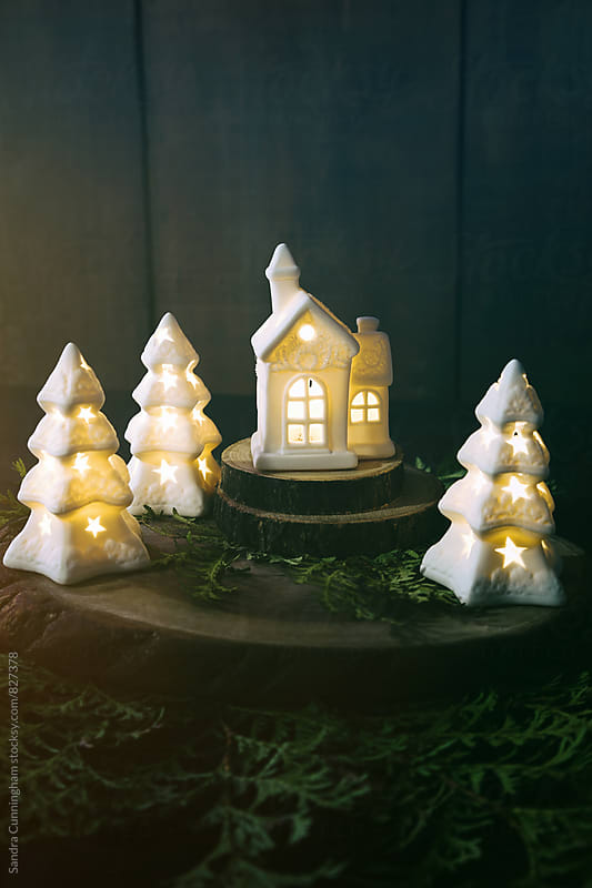 Little ceramic houses with lights and cedar branches by Sandra Cunningham for Stocksy United