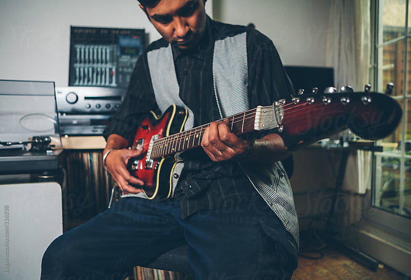 Asian musician playing a guitar in a home studio. by kkgas for Stocksy United