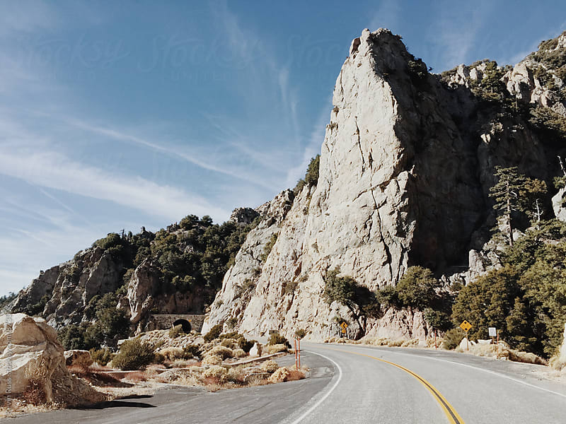 Big Rocky Peak on Rural Highway by Kevin Russ for Stocksy United