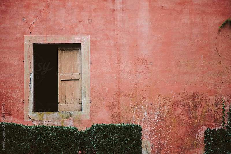 pink wall of a villa in Italy with window and hedge by Sarah Lalone for Stocksy United