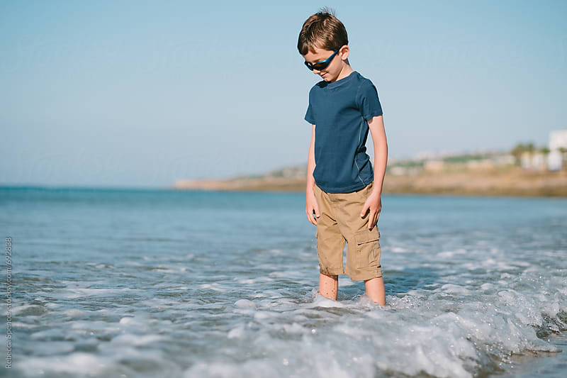 Child paddling in the sea by Rebecca Spencer for Stocksy United