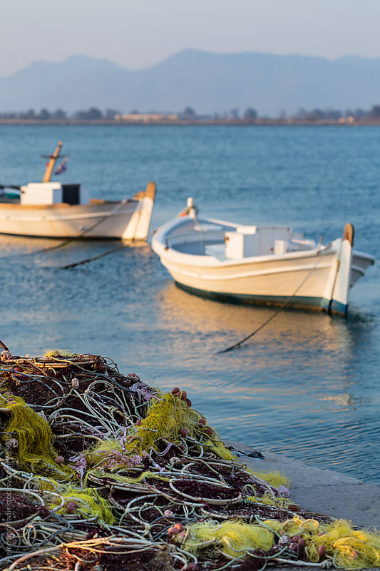 Fishing Nets with Boats in the Background by Helen Sotiriadis for Stocksy United